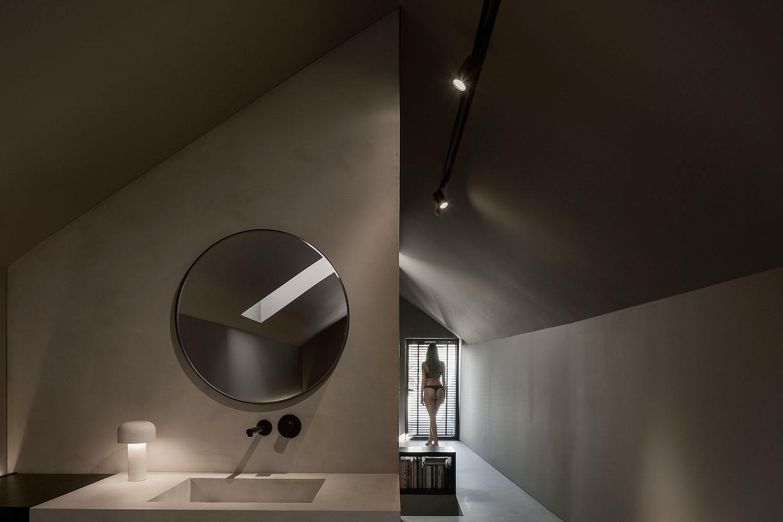 bathroom with circular mirror over washing basin