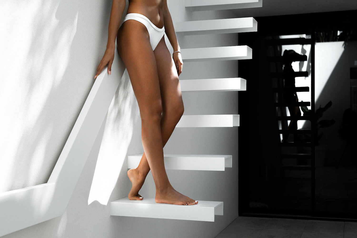 girl with bronzed legs and white bikini standing on stairs
