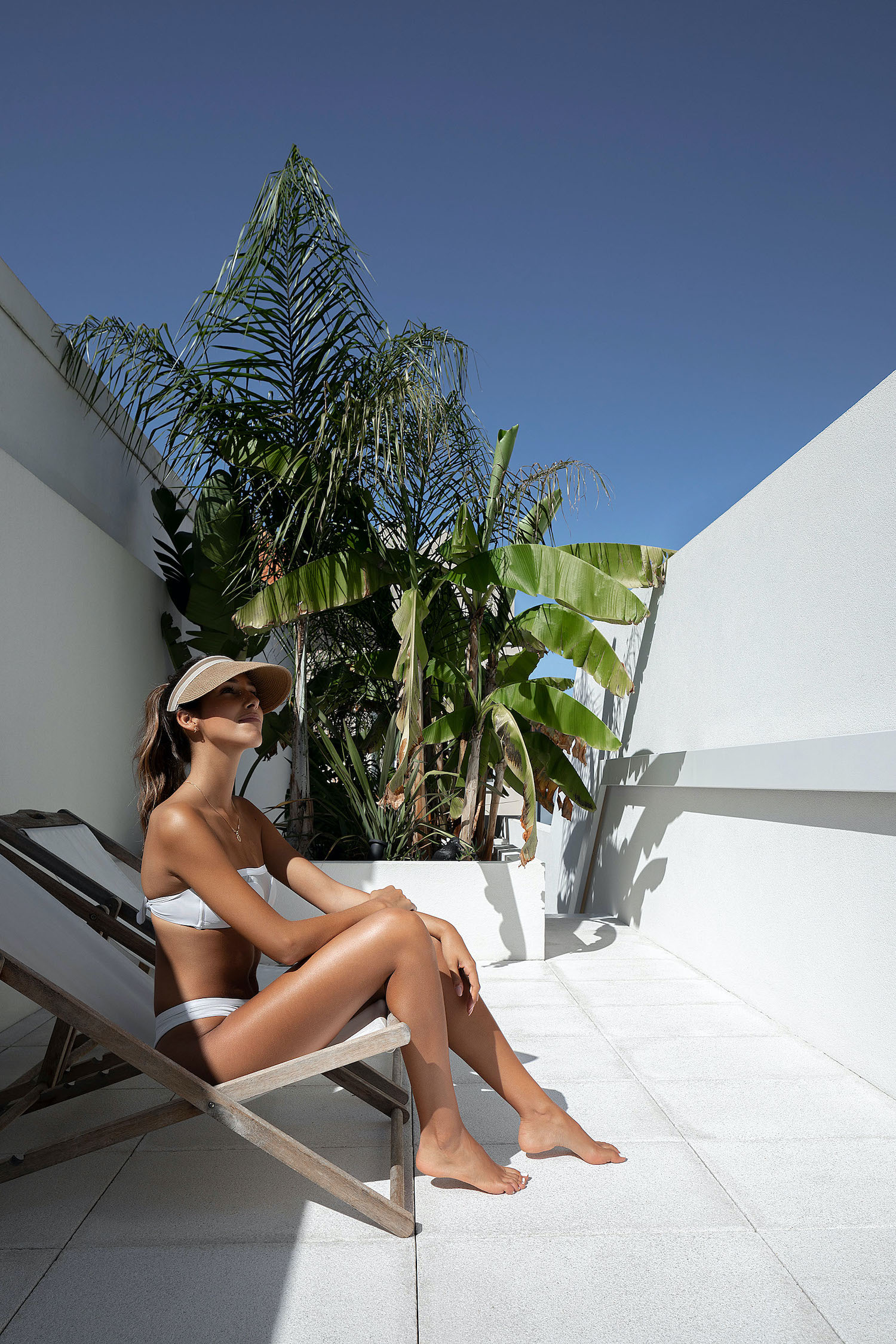 sexy girl with beautiful bronzed body taking sun on the roof of a small house