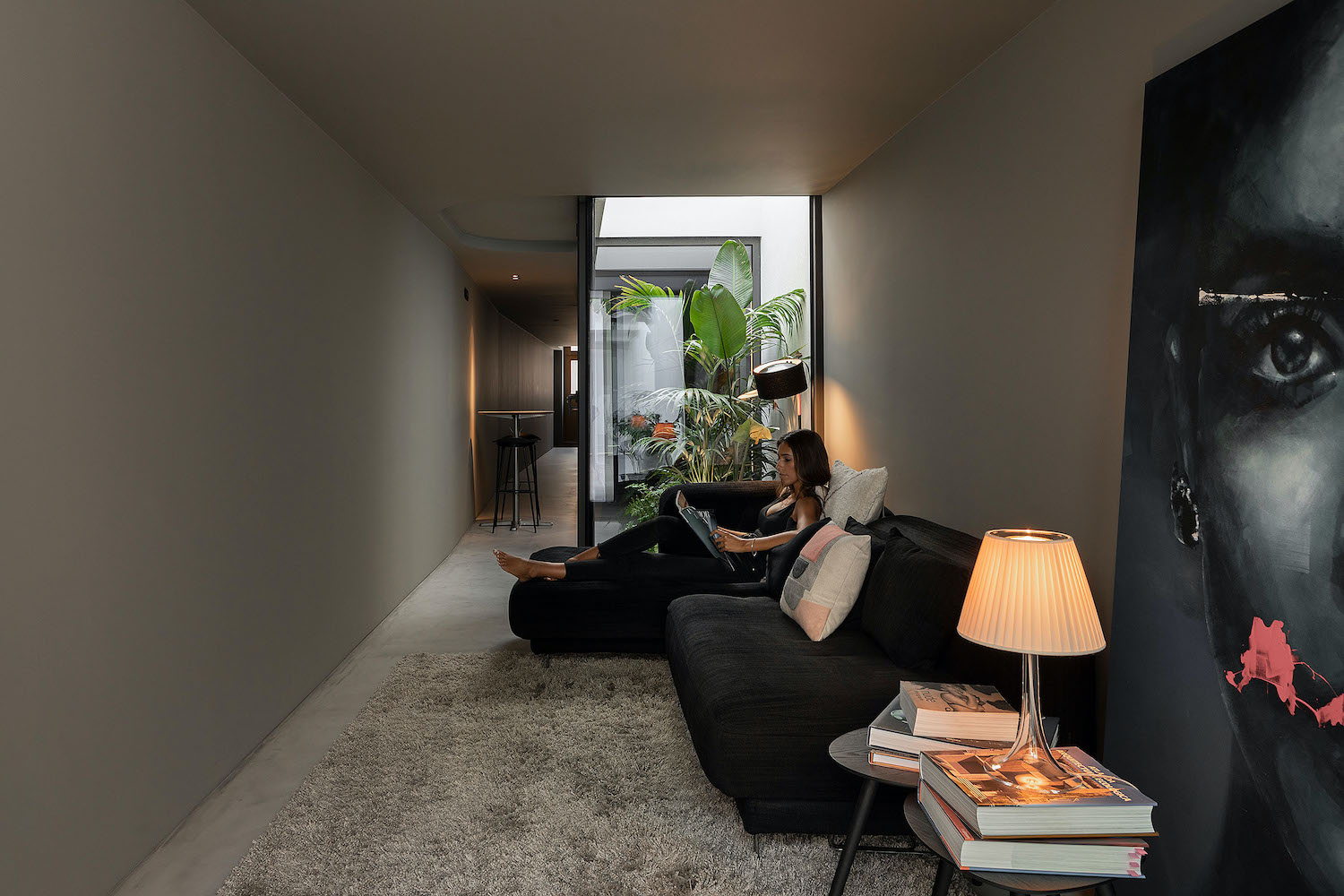 girl reading book while sitting on black sofa in living room