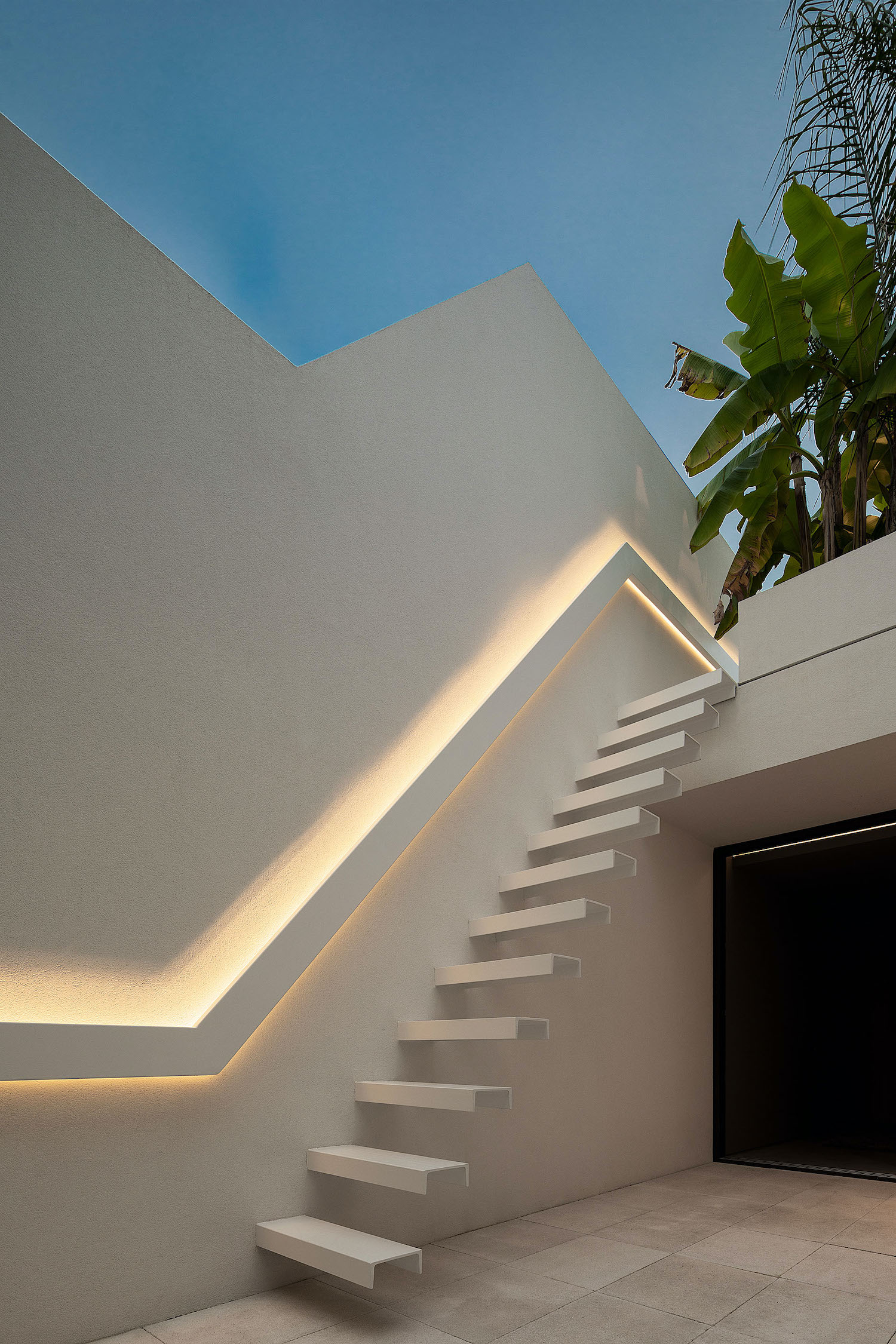 white staircase in the backyard of the house illuminated with led lighting