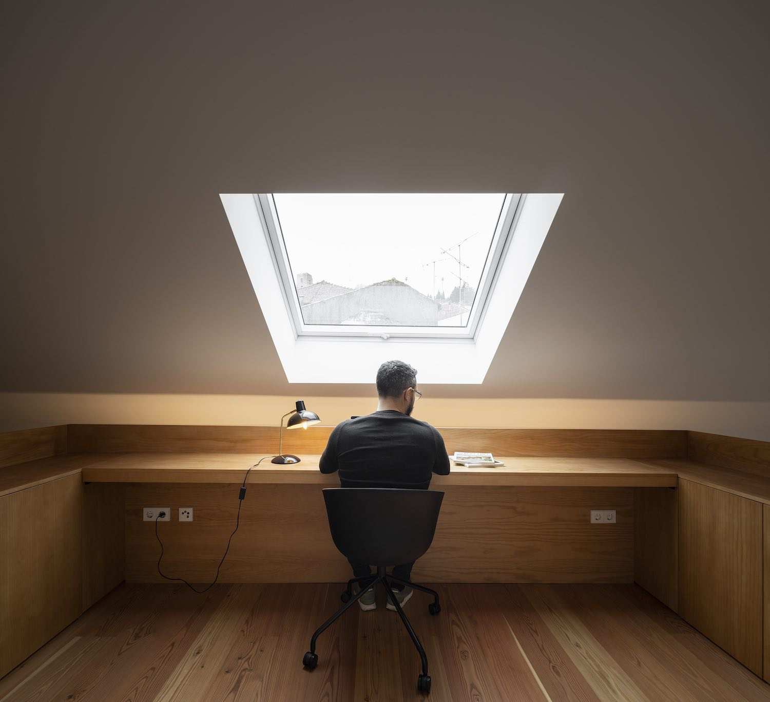 man working on his desk under window Lin the roof