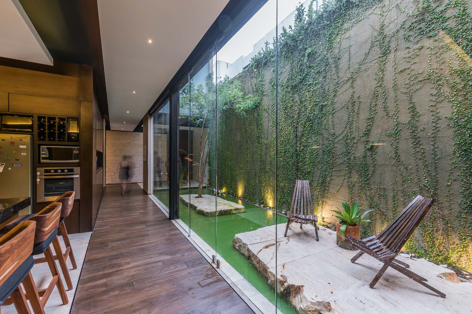 kitchen with glass wall near Courtyard with green wall in the center of the house