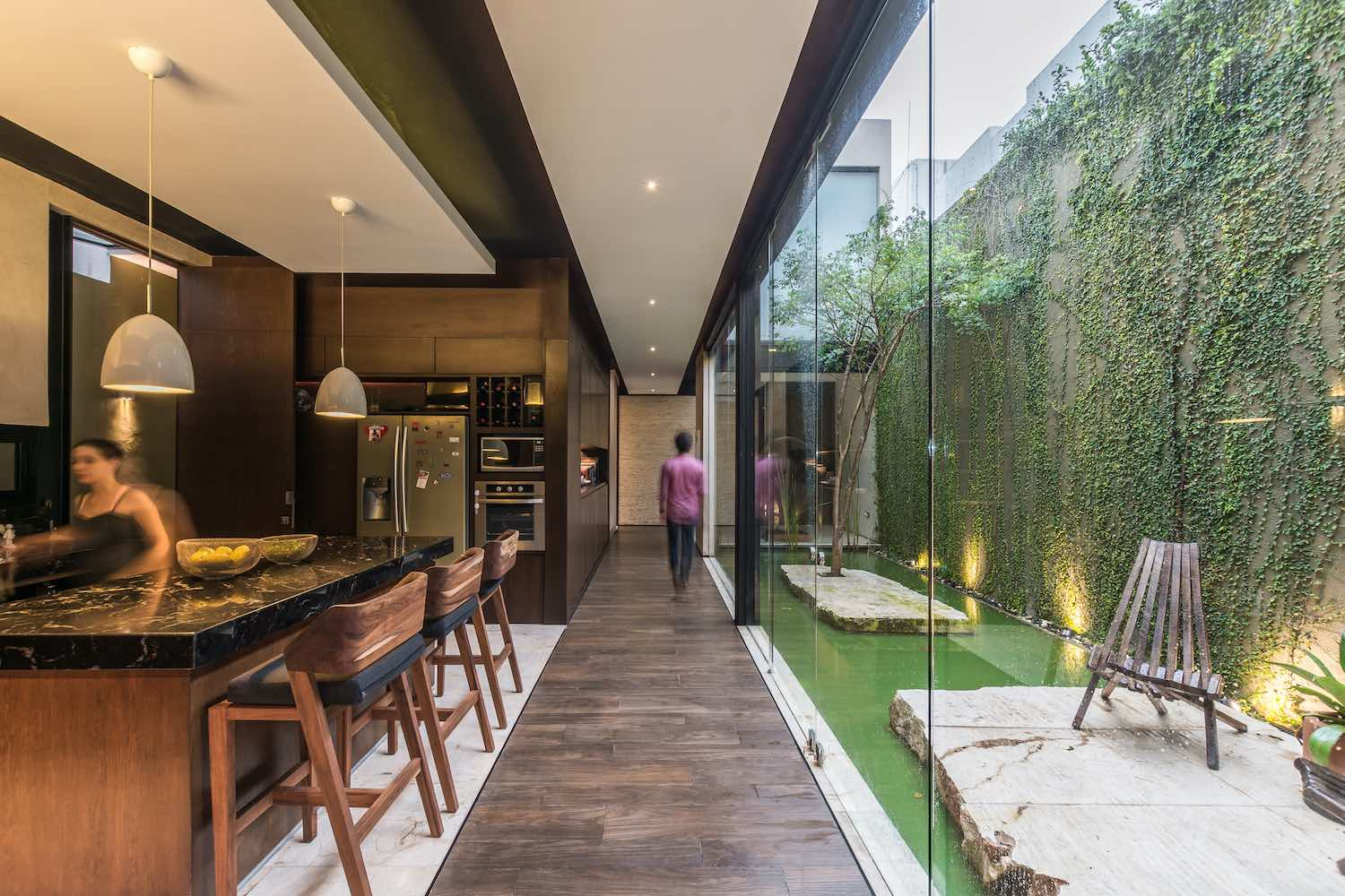 a big glass wall letting the natural lights enter the kitchen from interior courtyard
