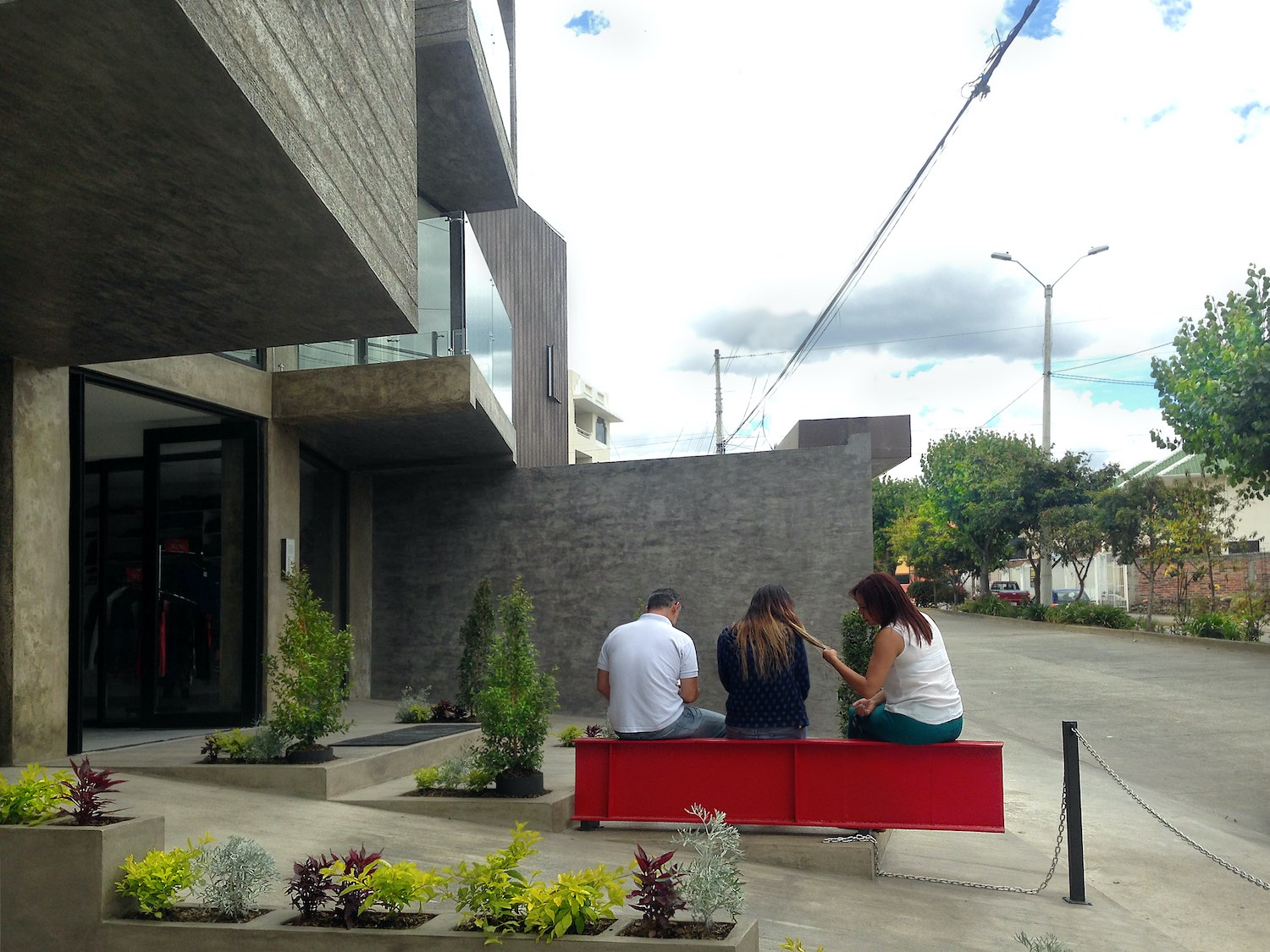two girls and a boy sitting on steel beam shaped bench in from of the building