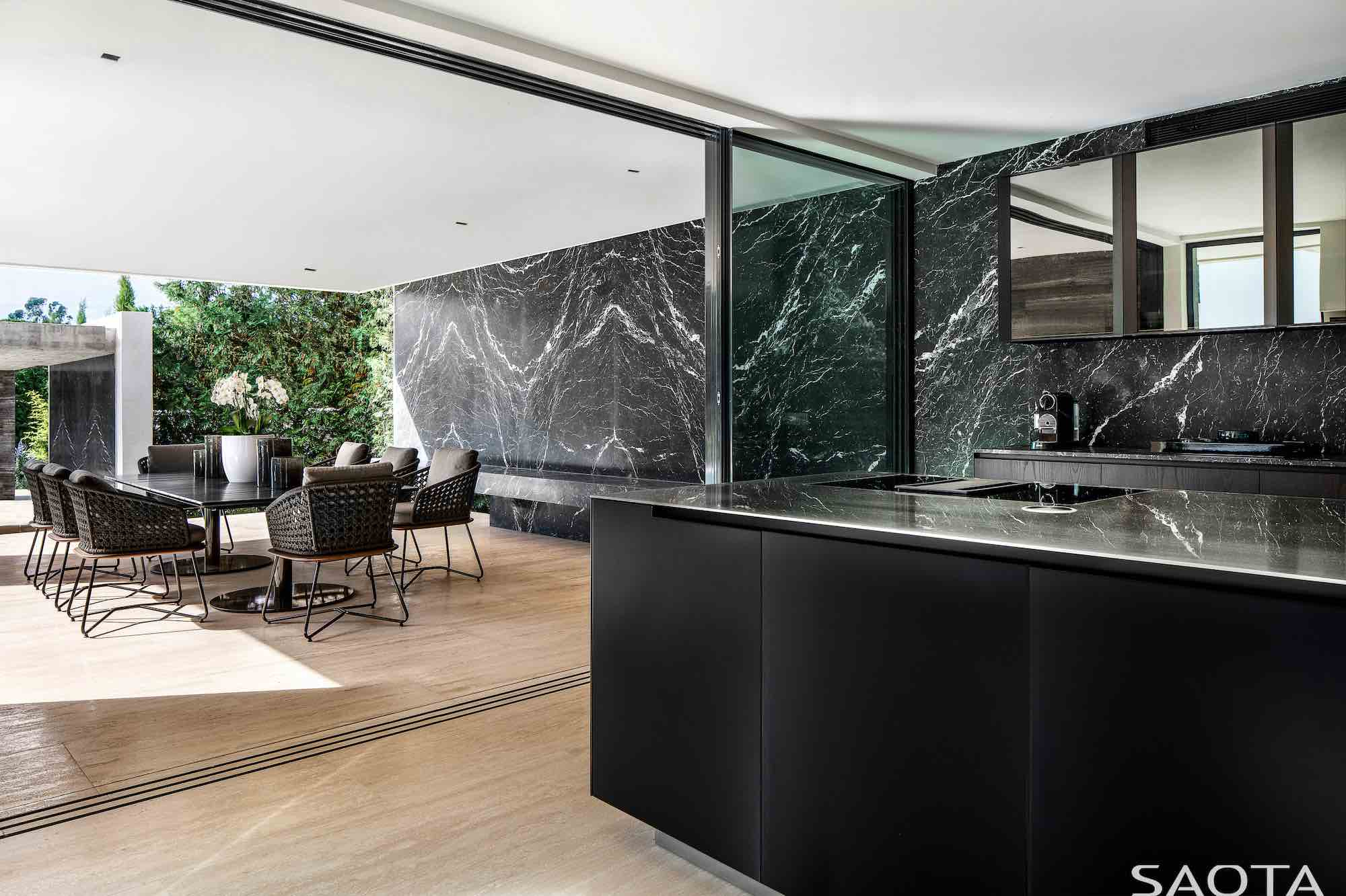 dining area with a glass table and black ceramic wall