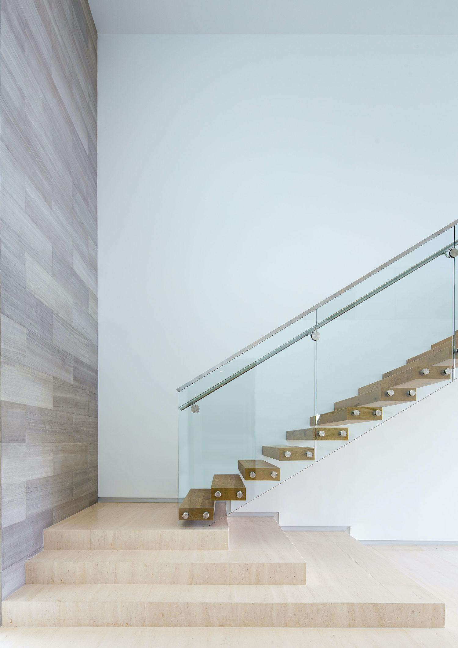 wooden staircase with glass handrail