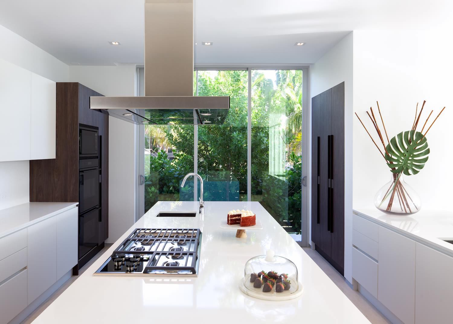 modern glossy white kitchen with windows toward garden