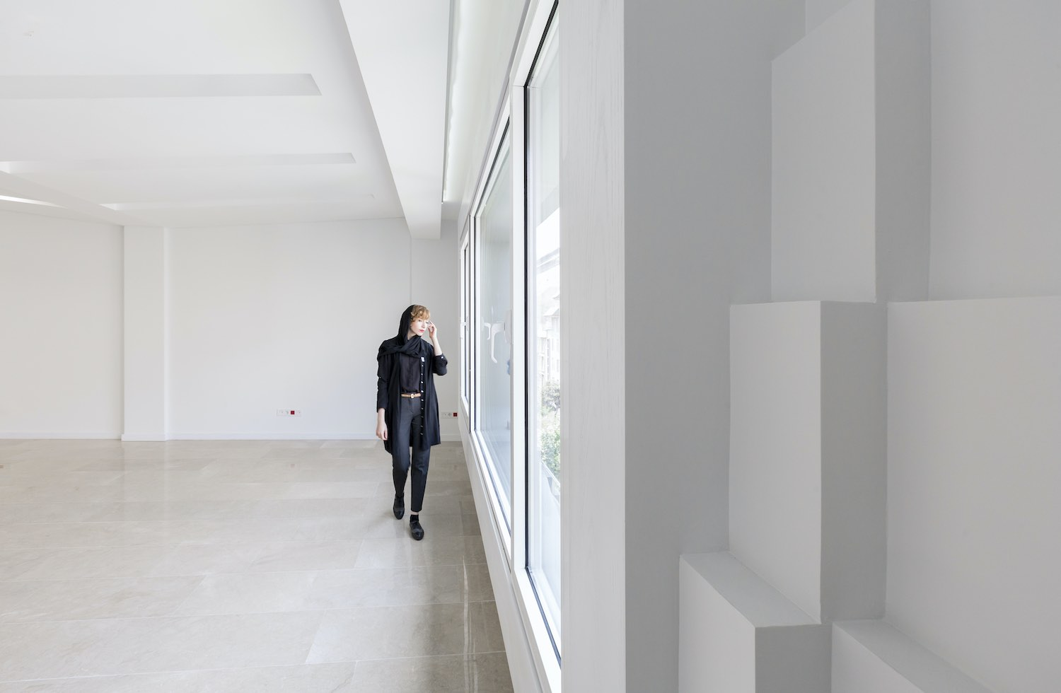 a woman with hijab walking in an empty room