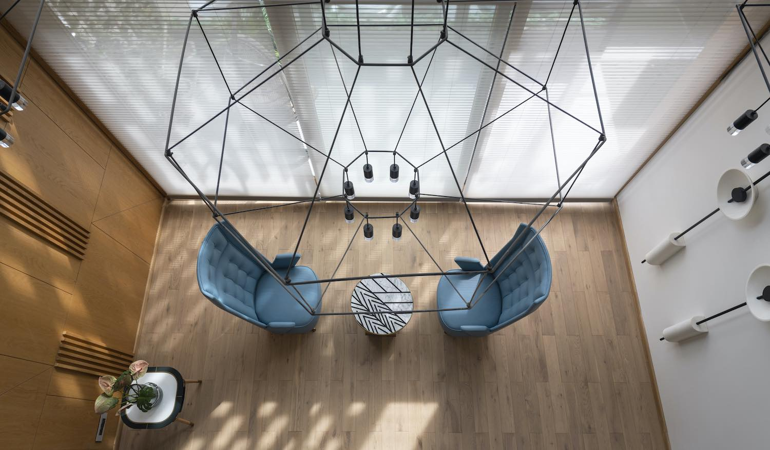 steel pendant lamp over blue armchairs