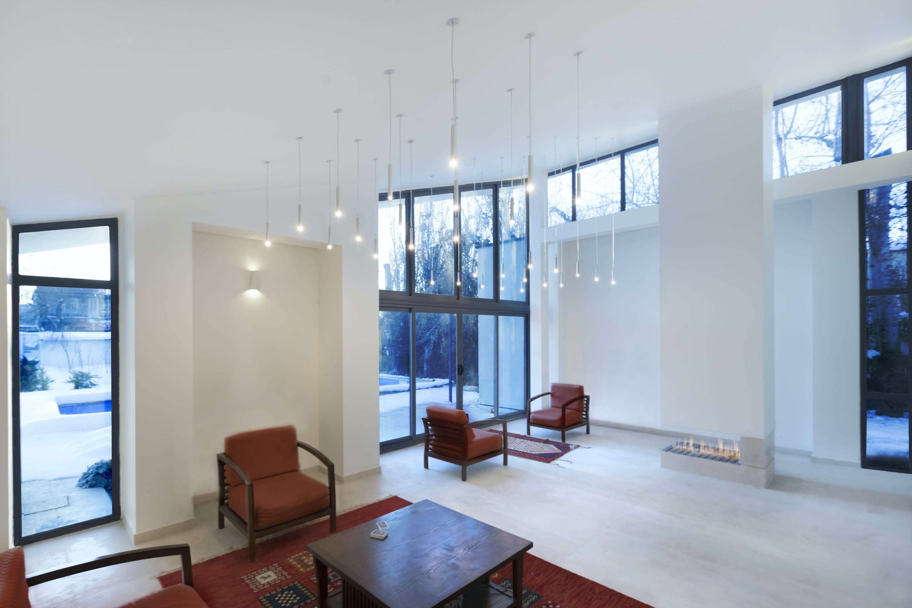 large pendant lamp hanged over tow read armchairs