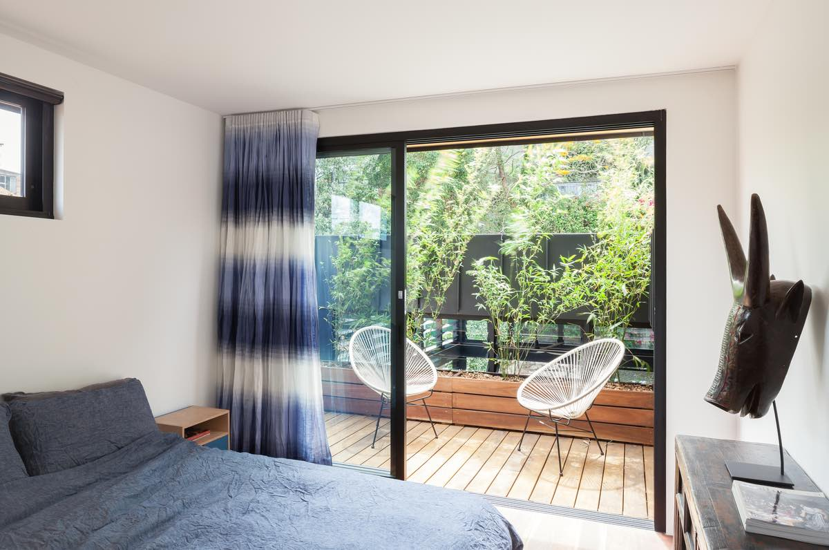 The bedroom with two chairs outside opened to a spectacular view