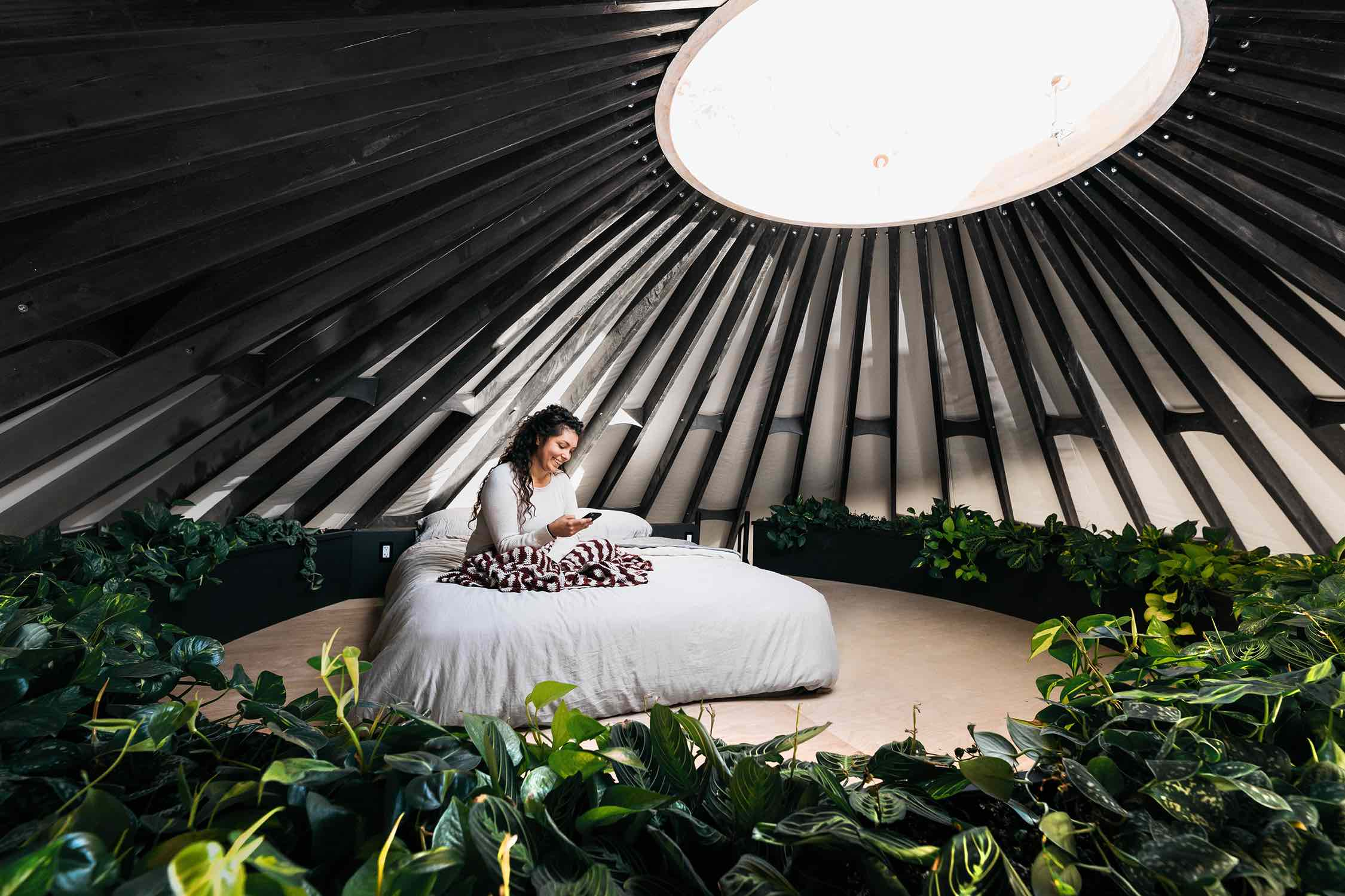 a girl texting on a bed with skylight over the bed