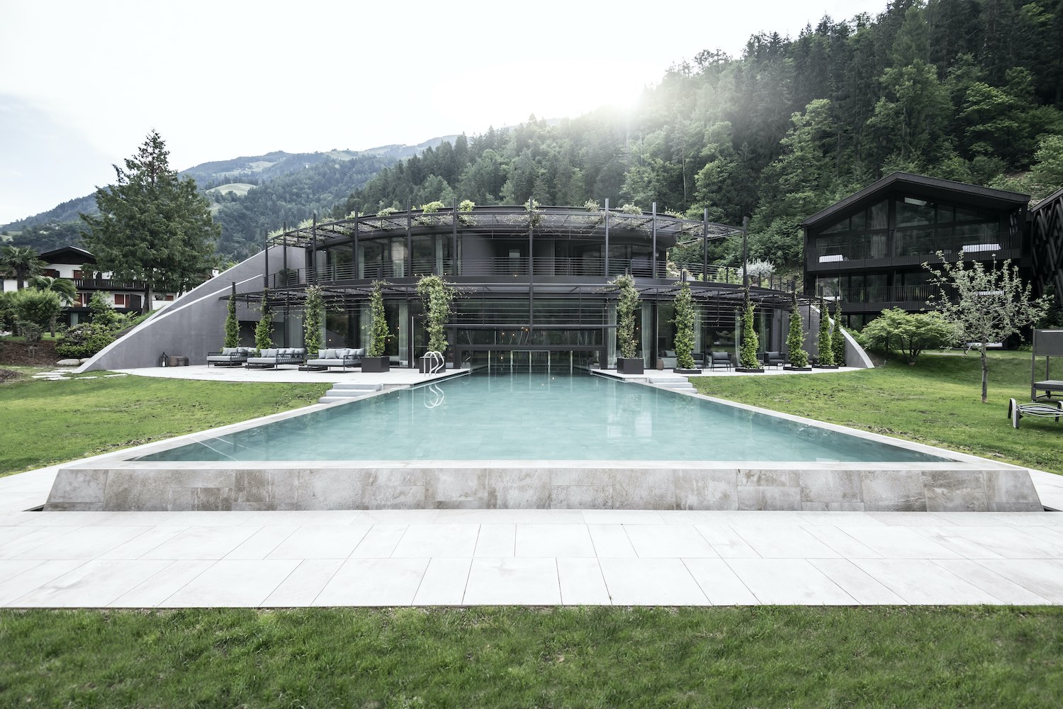 hotel with pool surrounded with green trees