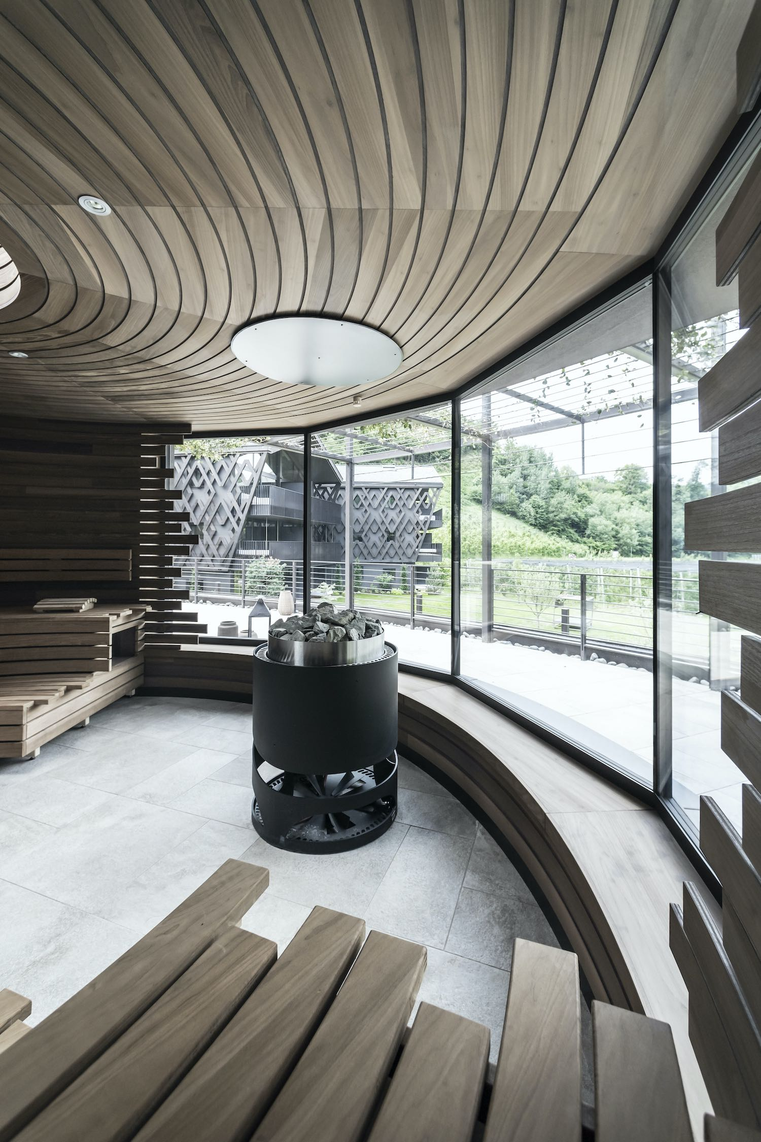 circular room with wooden benches and metallic fireplace