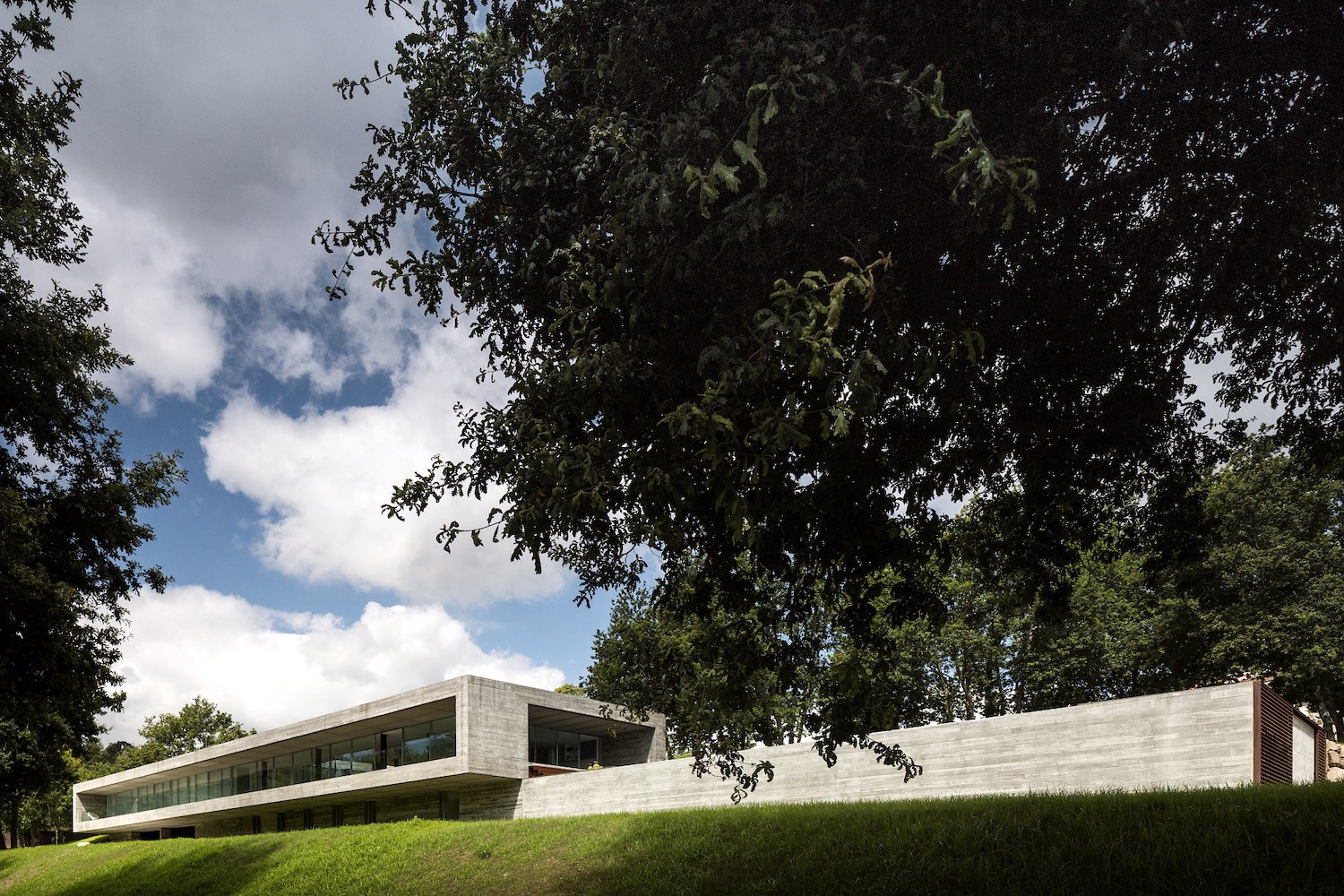 long concrete house on a greenery hill