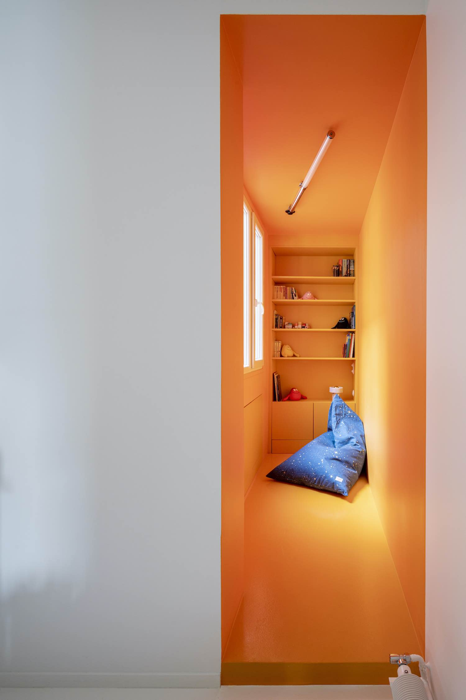 library located at the end of an orange wall corridor
